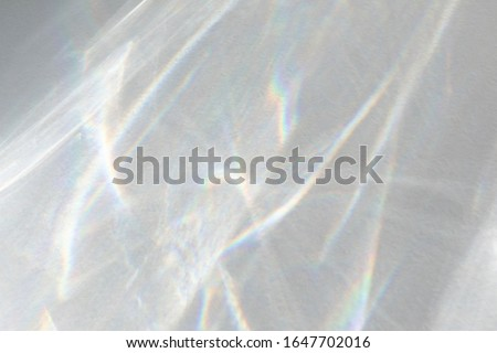 Water texture overlay effect for photo and mockups. Organic drop diagonal shadow caustic effect with rainbow refraction of light on a white wall. Royalty-Free Stock Photo #1647702016