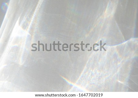 Water texture overlay effect for photo and mockups. Organic drop diagonal shadow caustic effect with rainbow refraction of light on a white wall.