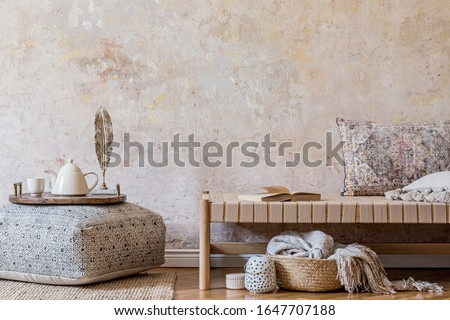 Stylish oriental living room interior with beige chaise longue, rattan decoration, big pouf with wooden tray and tea pot, book and elegant personal accessories. Wabi sabi concept. Copy space. Template Royalty-Free Stock Photo #1647707188