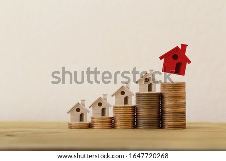Arrange red outstanding small house or home on stacks of coins, Property investment real estate / Home loan / asset refinancing concept : depicts a homeowner or a borrower turns properties into cash. #1647720268