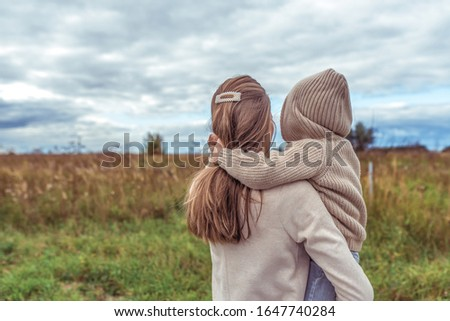 family woman mother holds her son in her arms, little boy in sweater with hood, rest in field, parenting child care love, parental support. Autumn spring day. Warm clothing. Free space for copy text #1647740284