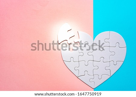 Heart shape puzzle on pink and blue background. Image of both thoughts. The last piece of the Heart shape puzzle. #1647750919