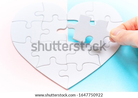 Heart shape puzzle on pink and blue background. Image of both thoughts. The last piece of the Heart shape puzzle. #1647750922