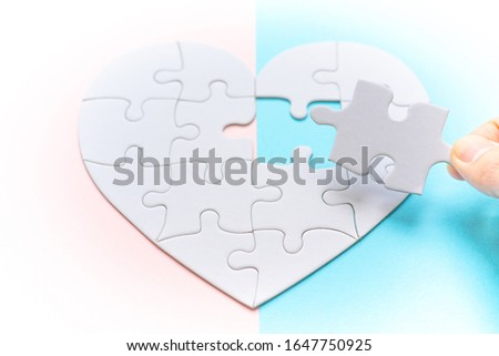 Heart shape puzzle on pink and blue background. Image of both thoughts. The last piece of the Heart shape puzzle. #1647750925