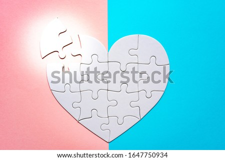 Heart shape puzzle on pink and blue background. Image of both thoughts. The last piece of the Heart shape puzzle. #1647750934