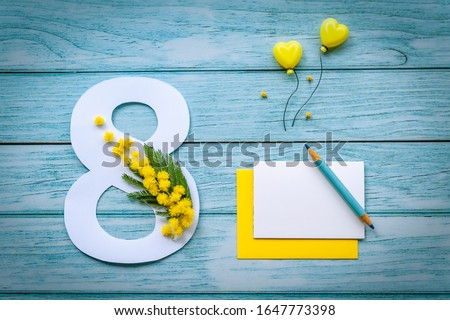 Greeting Card International Women's Day on March 8th. Branch of mimosa decorates the number eight and blank postcard with pencil on blue wooden background. Space for text. Soft focus. Top view. #1647773398