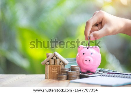 Piggy bank is placed on the calculator. house and coin placed on the side. planning savings money of coins to buy a home concept for property, mortgage and real estate investment.to buy a house. #1647789334