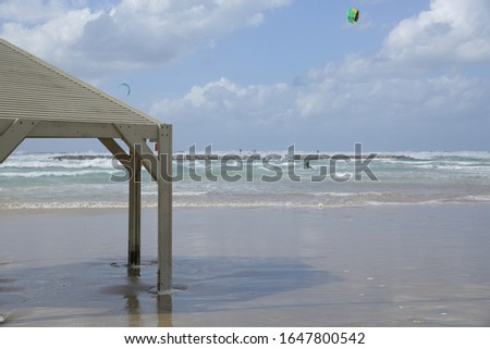 wooden canopy or umbrella on the sand by the sea or ocean on the background of the sea with kitesurfer #1647800542