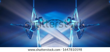 Athletic gymnastic Brazilian man doing aerial silks Performance with white and blue light, picture with mirror effect. Strong and flexible body.