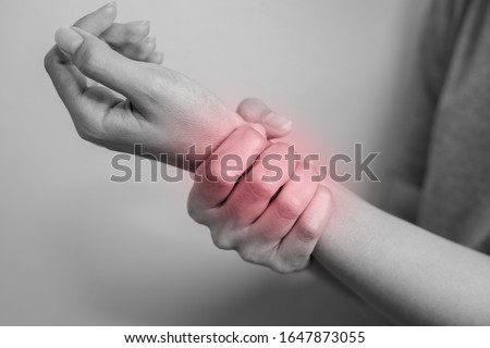 Woman suffering from pain in wrist. Pain in a women wrist. Young woman holding her painful wrist on wall background. #1647873055