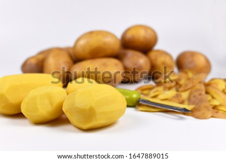 Food preperation with peeled potatos, peels and whole potatoes in background #1647889015
