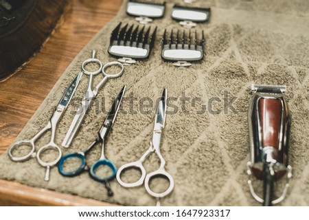Barber tool in barbershop. Hairdresser tool. Scissors, combs, razors, clippers. Tool for the wizard. Organization of the workplace. Selective focus #1647923317