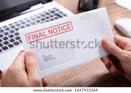 Close-up Of Person's Hand Holding Final Notice Envelope Royalty-Free Stock Photo #1647933364
