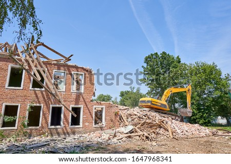 Destroyed old house and a yellow excavator on the wreckage. Demolition of an old house with brick walls Royalty-Free Stock Photo #1647968341