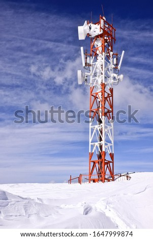 Cellular mast high in snow-covered mountains #1647999874