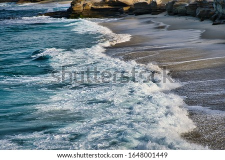 WAVES IN THE PACIFIC OCEAN CRASHING ONTO THE BEACH AND ROCKS IN LA JOLLA CALIFORNIA NEAR SAN DIEGO CALIFORNIA #1648001449