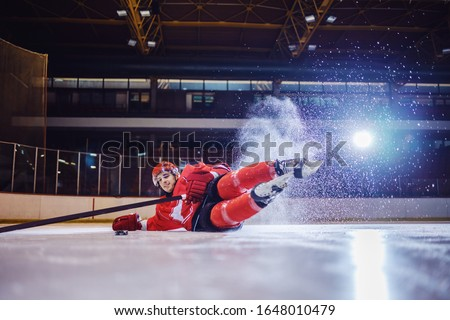 Strong hockey player falling on ice in attempt to receive puck from teammate. #1648010479