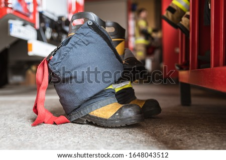 Firefighter's shoes and pants and a wardrobe cabinet, fire truck and fireman in the background