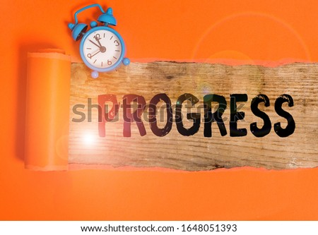 Handwriting text writing Progress. Concept meaning development towards an improved or more advanced condition Alarm clock and torn cardboard placed above a wooden classic table backdrop. #1648051393