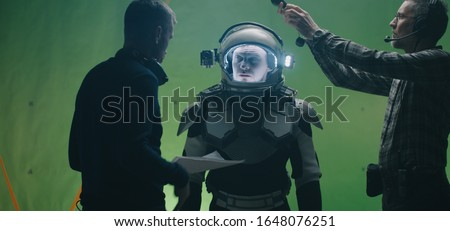 Medium shot of a director giving instructions to an actor while a technician using his light meter on a film set