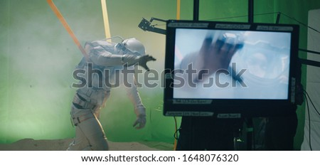 Medium shot of the shooting of a scene with an astronaut struggling against the wind