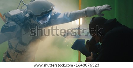 Medium shot of a shooting a scene with an astronaut struggling against the wind