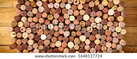 Very high resolution photo of standing red wines used corks arranged in rows and columns on wooden rustic background. All specific terms were removed.