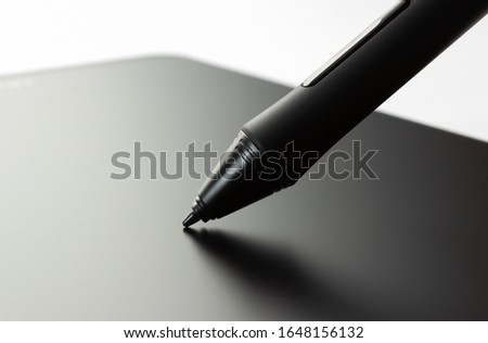 Pen on graphic tablet. Side view on white background. Tool for illustrators and designers. #1648156132