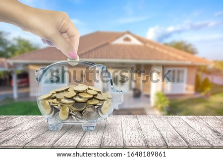 Hand that is coin down transparent piggy bank. Home blurred background. planning savings money of coins to buy a home concept for property, mortgage and real estate investment. #1648189861