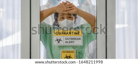 coronavirus covid 19 infected patient in coronavirus covid 19 quarantine room with quarantine and outbreak alert sign at hospital with blurred disease control experts, coronavirus outbreak control Royalty-Free Stock Photo #1648211998