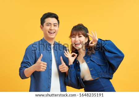 Excited beautiful asian couple shows thumb up gesture agree to do something and collaborate against orange wall, did great job, show approval, like idea. Everything will be OK. #1648235191