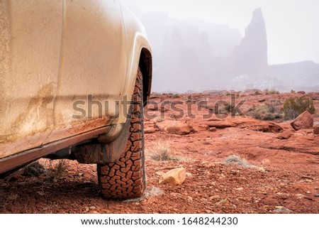 4x4 SUV car or truck driving on a trail in winter conditions - Fisher Towers in Moab area, Utah, off-road driving, recreation and travel concept #1648244230