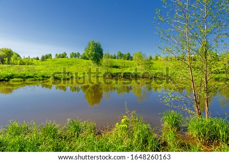 The lake is a large body of water surrounded by land. Walnut and pine trees grow along the edge, complete calm, beautiful hatching in the water #1648260163