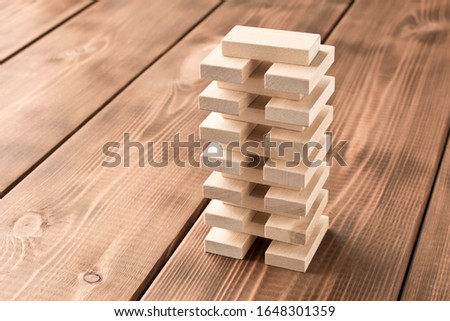 A pyramid of dominoes. Playing dominoes on a wooden table. The concept of the games is to relax. Selective focus #1648301359