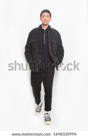 handsome young man walking with a hand in his pocket wearing black clothes, pants standing isolated on white background; full body, full length    #1648320994