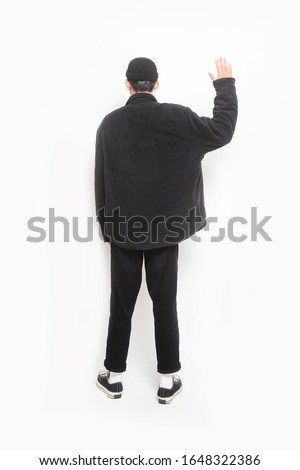 Back view handsome young man walking with a hand in his pocket wearing black clothes, pants standing doing stop sing with palm of the hand isolated on white background; full body, full length    #1648322386