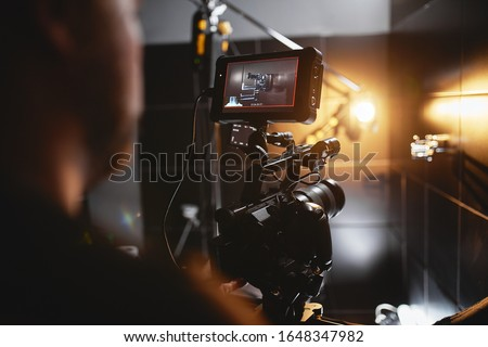 Video production backstage. Behind the scenes of creating video content, a professional team of cameramen with a director filming commercial ads. Video content creation, video creation industry. Low Royalty-Free Stock Photo #1648347982