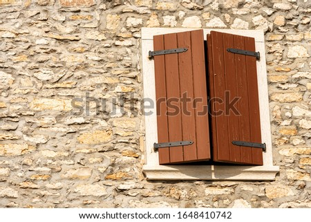 Close-up of a window with closed wooden shutters on a stone wall. Veneto, Verona province, Italy, Europe #1648410742