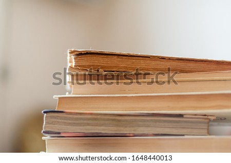 A stack of old books on a desk in a library. Side view of 6 battered textbooks. Free space for text. Close-up. Selective focus. Landscape photo arrangement.