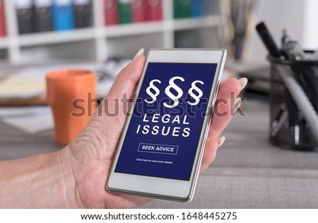 Female hand holding a smartphone with legal issues concept Royalty-Free Stock Photo #1648445275
