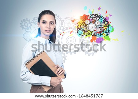 Serious young woman with dark hair and notebooks standing near concrete wall with colorful brain with gears drawn on it. Concept of brainstorming and education. #1648451767