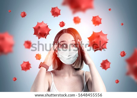 Scared young woman in medical mask standing over gray background with blurry red virus molecules. Concept of coronavirus and Asian flu panic. Toned image #1648455556