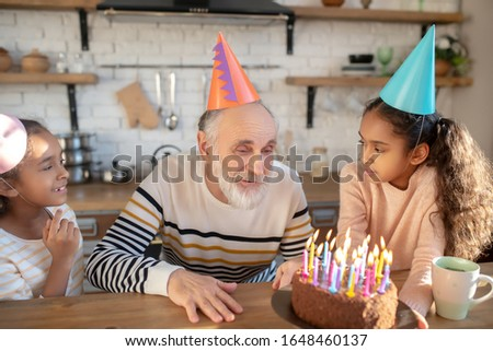 Bday party. Bearded man in a birthday hat having his birthday with his granddaughters