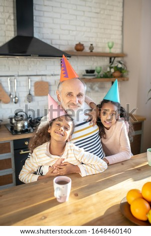 Harmony. Two dark-skinned girls in bday hats feeling happy with their granddad