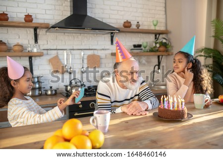 Bday celebration. Bearded man in a birthday hat celebrating his birthday with his granddaughters