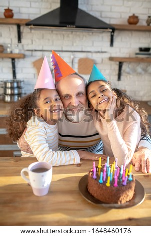Bday party. Bearded grey-haired man and his dark-skinned girls celebrating bithday