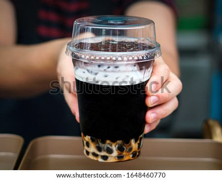 At boba tea store,  saleman is handing a glass of chocolate boba tea with ice towards cumstomer. Serving a beverages to customers.  #1648460770