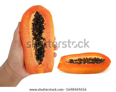 Male hand holding a half of ripe papaya and half of ripe papaya fruit with seeds isolated on white background #1648469656
