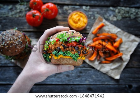Hand holding vegan sweet potato black bean burger with kale leaves, vegan cheese sauce, micro greens and rye buns. Clean eating, plant based food concept Royalty-Free Stock Photo #1648471942