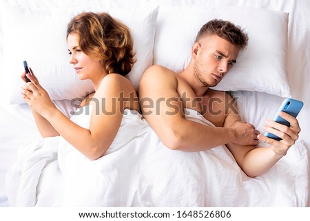 Young couple in bed with mobile phones lie resting, write a message online. A man and a woman lay with their backs to each other, each using his mobile smartphone. chat sms messages. #1648526806